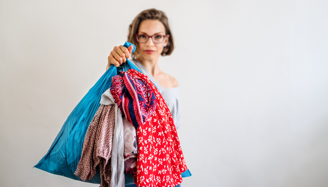 A front view portrait of woman indoors holding bag with old clothes.