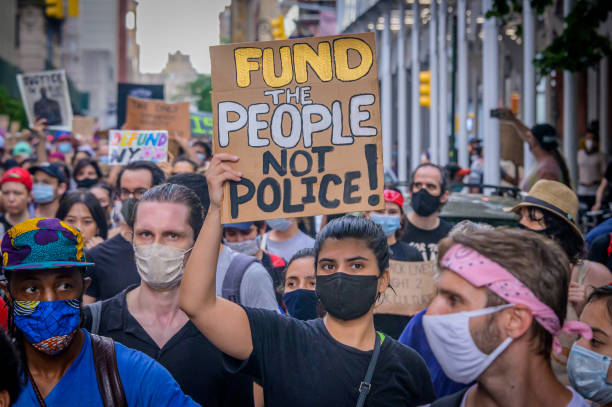 A participant holding a Defund Police sign at the protest. On the eve of the NYC budget decision, hundreds of protesters gathered at Washington Square Park for a massive march to City Hall.