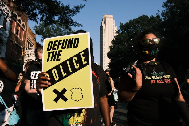 """A protester carrying a sign that reads """"Defund The Police"""" during the Black Women Matter """"Say Her Name"""" march on July 3, 2020 in Richmond, Virginia."""