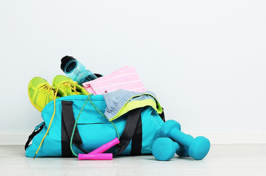 Sports bag with sports equipment in room
